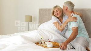 Romantic husband bringing his happy wife breakfast in bed