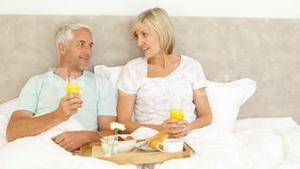 Couple enjoying breakfast in bed together
