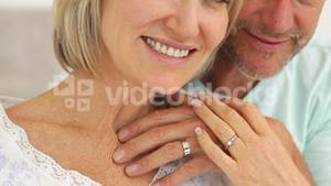 Married couple embracing and smiling at camera in bed together
