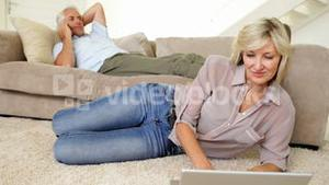 Woman using laptop with partner talking on phone on the couch