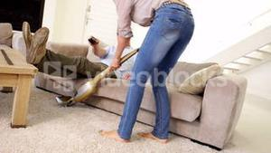 Woman hoovering the carpet while partner relaxes watching tv