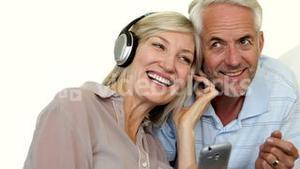 Cute mature couple listening to music together
