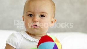 Cute baby girl playing with soft ball on bed