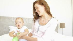 Smiling young mother feeding her baby girl her bottle