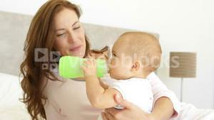 Smiling young mother watching her baby girl drink her bottle