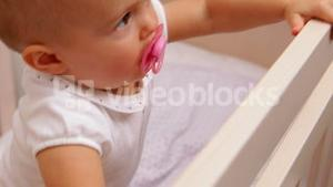 Cute baby girl standing up in her cot