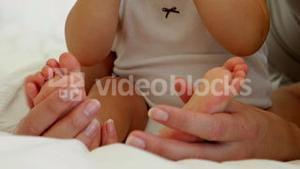 Mother touching her baby daughters tiny toes