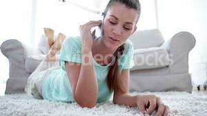 Pretty woman lying on floor chatting on the phone