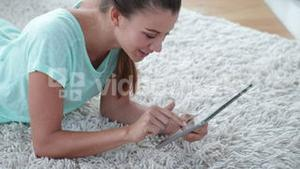 Pretty woman lying on floor using her tablet pc