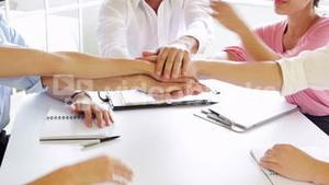 Business people putting their hands together during meeting