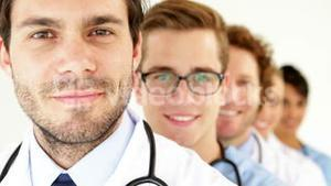 Team of doctors standing in row smiling at camera