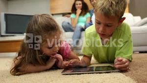 Sibings lying on floor using tablet with parents behind them on sofa