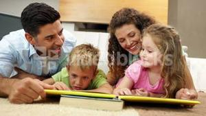 Siblings lying on floor reading book with parents
