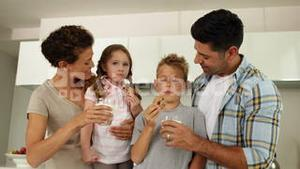 Children having milk and cookies with their parents