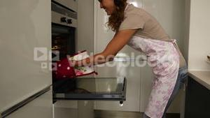 Woman taking hot cookies out of the oven