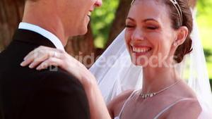 Young newlyweds dancing together and smiling at camera