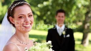 Pretty bride smiling at camera with groom standing in background
