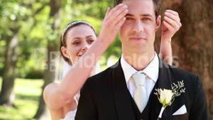 Bride covering her grooms eyes and smiling at camera