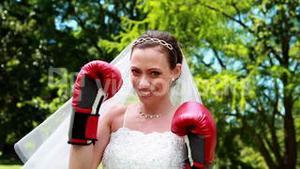 Pretty bride smiling at camera and wearing boxing gloves