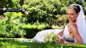 Pretty bride smiling at camera lying on the grass