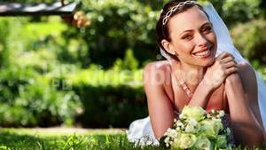 Beautiful bride smiling at camera lying on the grass