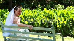 Beautiful bride smiling at camera sitting on bench