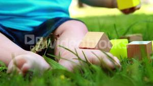 Baby playing with building blocks on the grass