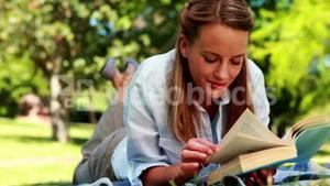 Pretty blonde reading a book lying on a blanket in the park