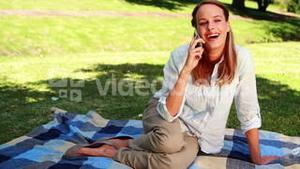 Pretty blonde sitting on a blanket in the park chatting on the phone
