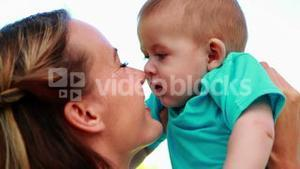 Happy mother rubbing noses with cute baby son in the park