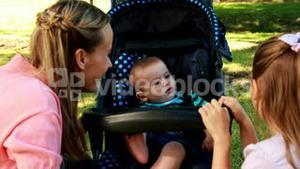 Mother and daughter playing with baby in a pram in the park