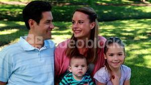 Young family smiling at the camera in the park