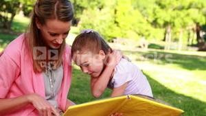 Little girl reading storybook with her mother in the park