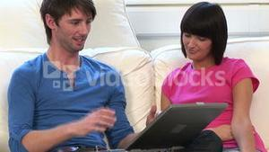 Young Couple on Sofa With Laptop
