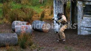 Man running out from shelter and getting shot at paintball