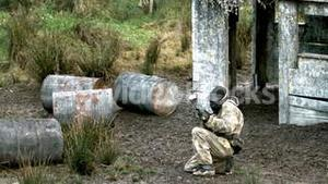Man crouching on ground and getting shot at paintball