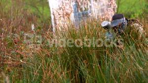 Man crouching in the grass shooting paintball gun