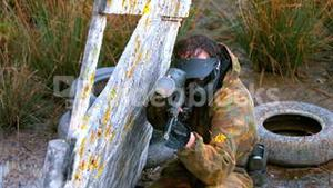 Man crouching behind fence shooting paintball gun