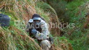 Man kneeling on ground shooting paintball gun