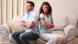 Couple sitting on couch not talking after a fight
