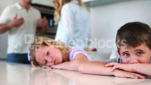 Young siblings blocking out noise from parents fighting