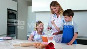 Happy mother and children making a cake together