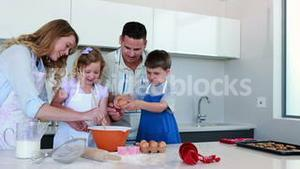 Happy young family making a cake together