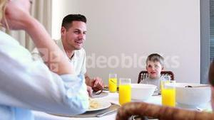 Happy young family talking at the dinner table