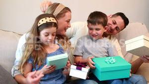 Happy young family sitting on sofa with birthday presents