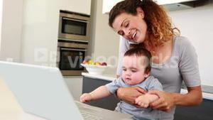 Mother sitting with baby boy on lap using laptop and talking on phone