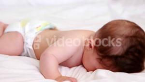 Baby in diaper crawling on bed