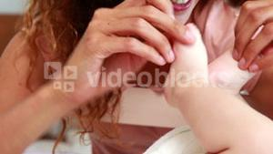 Smiling mother playing with baby sons feet in his crib