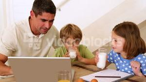 Father and children using laptop together at the breakfast table