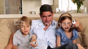Cute children playing video games with their father on the sofa